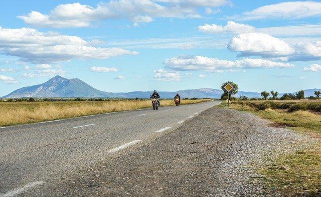 Dvaja ľudia idúci na motorkách s prilbou na hlave