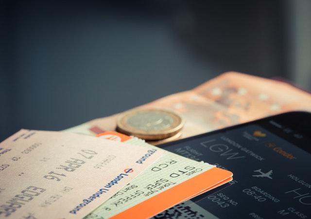 Letenky a peniaze položené na letáku z letiska.jpg