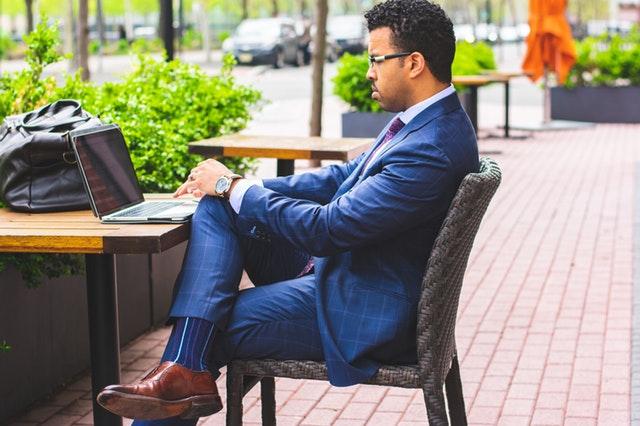 Muž v modrom obleku sedí za stolom a píše na počítači