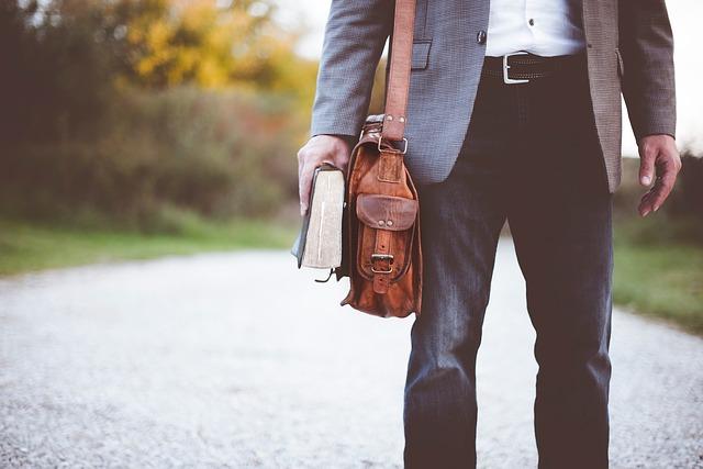Muž v sivom obleku s koženou taškou na ramene a knihou v ruke