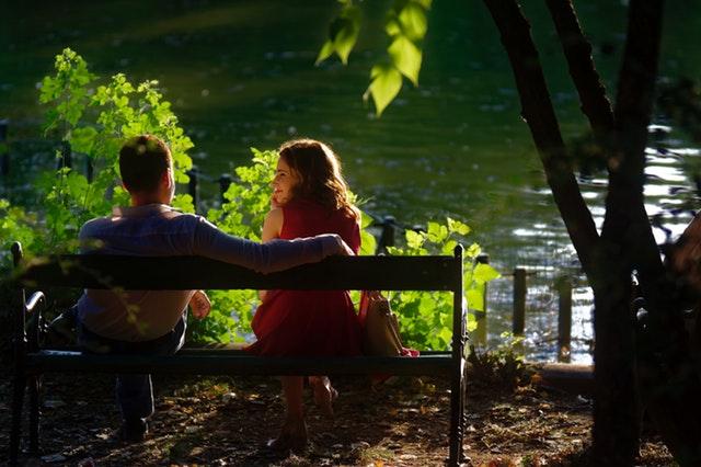 Muž a žena sedia na lavičke vedľa jazera a usmievajú sa na seba