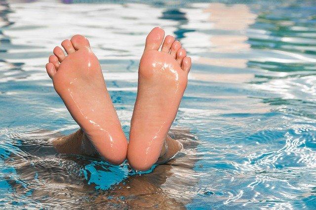 Ľudské chodidlá trčiace z vody v bazéne.jpg
