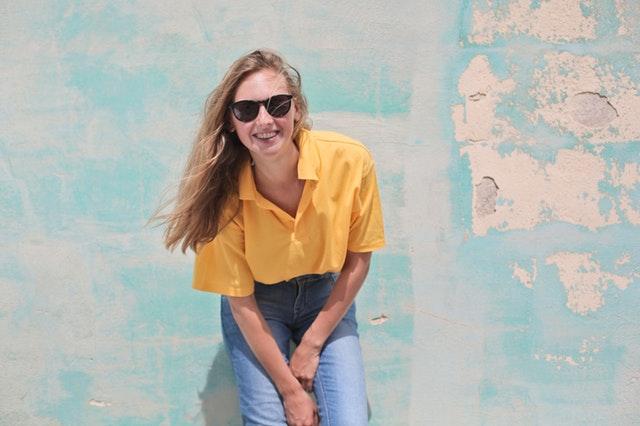 Žena v žltom tričku so slnečnými okuliarmi stojí pri stene.jpg